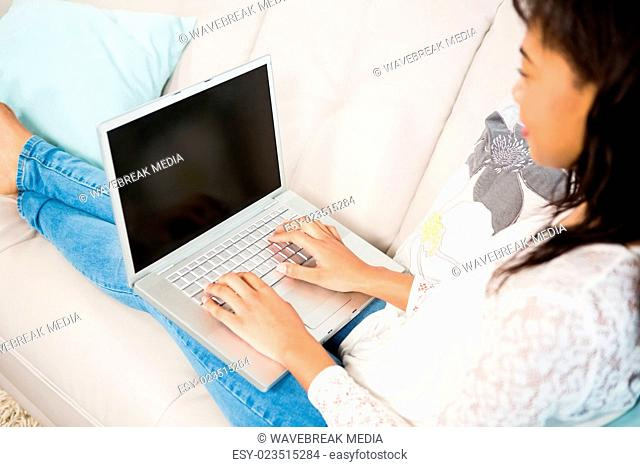 Casual smiling woman using laptop on the couch
