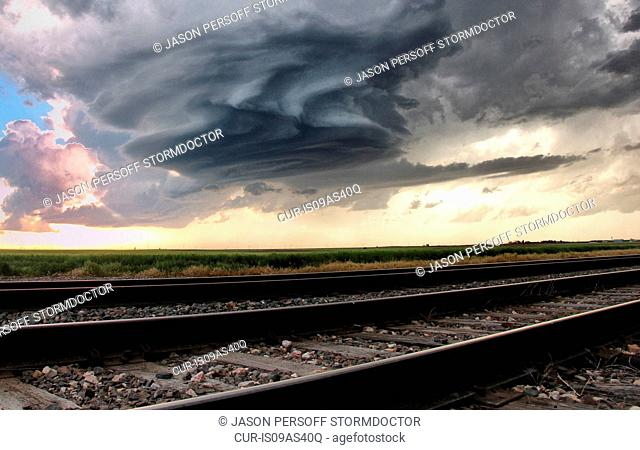 Fascinating mesocyclone rotating, crystal blue skies and bright sunshine in background, train tracks in foreground, Sidney, Nebraska, USA