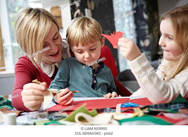Mother and two children drawing at kitchen table