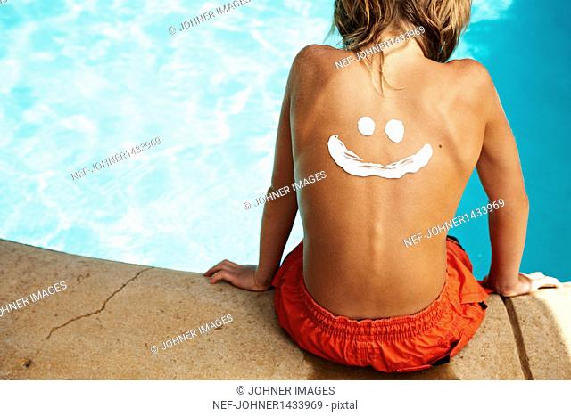 Boy with smiley face made with suntan lotion on back