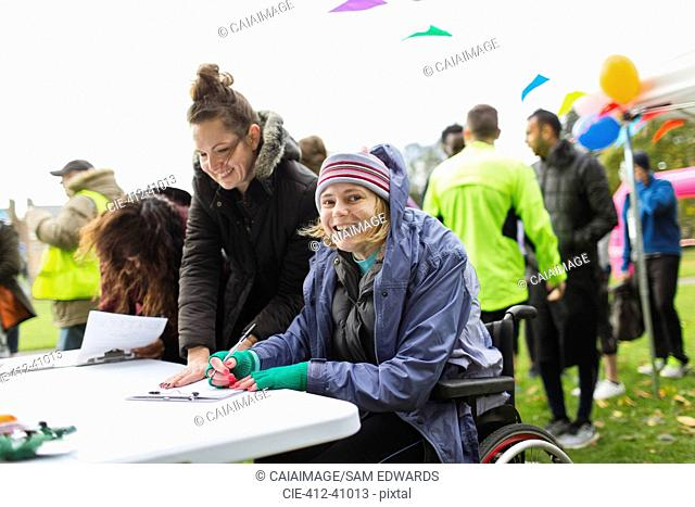 Portrait smiling woman in wheelchair checking in for charity race in park