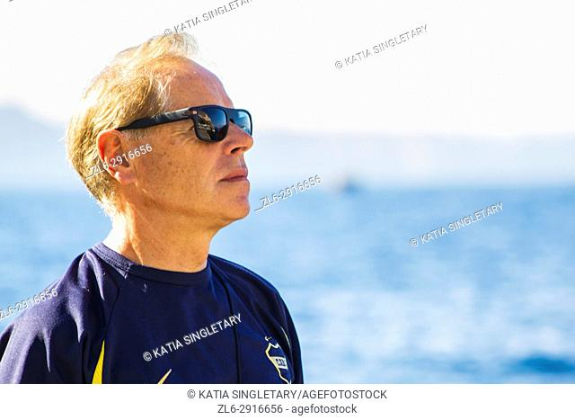 Caucasian retired senior with sunglasses looking thoughtful with the ocean and horizon in the background