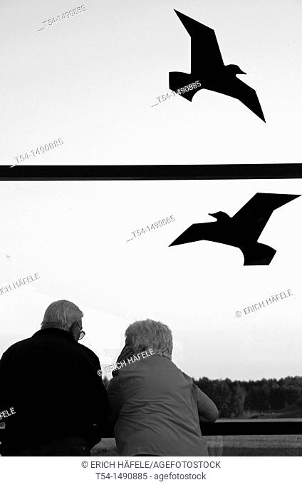 A couple stands at the airport and watch airplanes