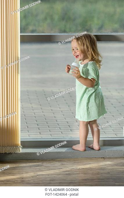 Full length of girl holding baby bottle while standing by window