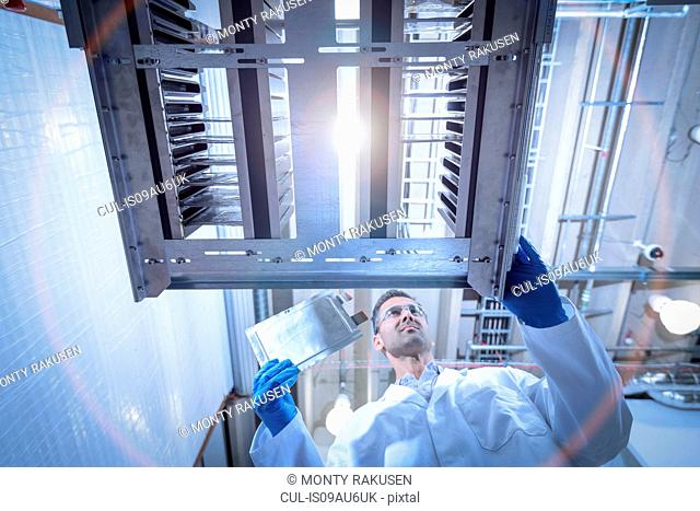 Scientist with lithium ion pouch cell manufacture machine in battery research facility, low angle view