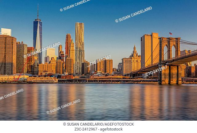 World Trade Center And The Brooklyn Bridge - A view to the midtown Manhattan, New York City skyline during the first light at sunrise