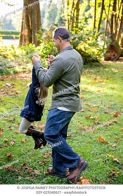 Dad swinging his young daughter around by the arms while playing and having fun at a nature park