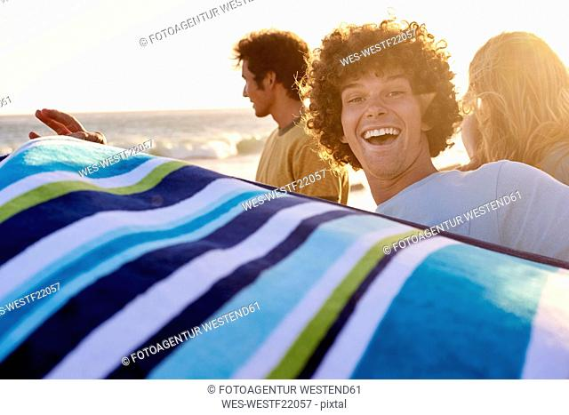 Happy young man with towel on the beach