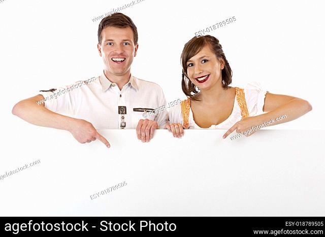 Junger Mann und Frau im Dirndl zeigen auf Werbefläche