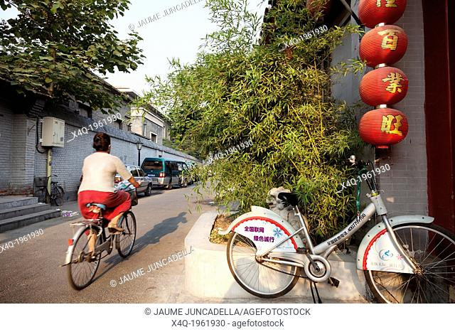 China, Beijing - August 17, 2010. A Chinese leaves with his bicycle to work early in the morning through the old hutong of de city