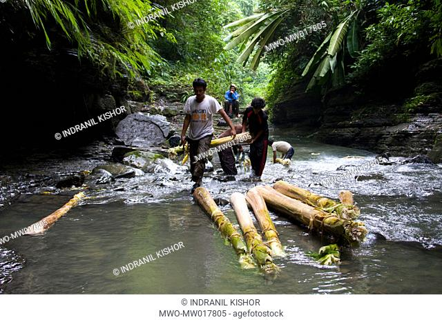 The Bangladesh Tourism Expansion Forum, BTEF members making a banana raft, on the bank of a creek, near Remarki, in Thanchi, Bandarban, Bangladesh October 4