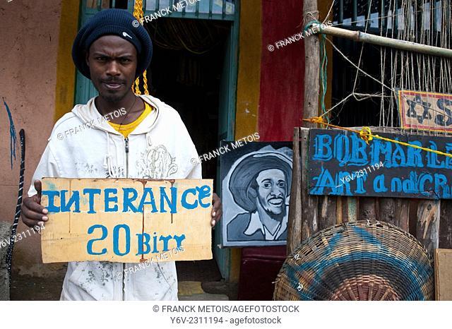 Rasta young man holding a entrance 20 birr panel in front of the shop where he sells Rasta art. Shashemene ( Ethiopia)
