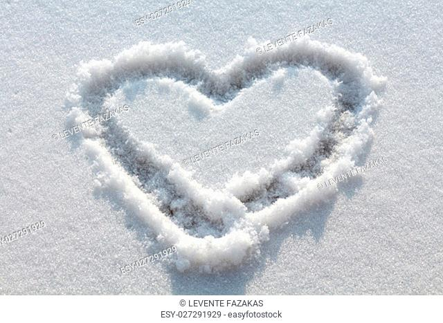 Heart drawn in white snow and sunshine