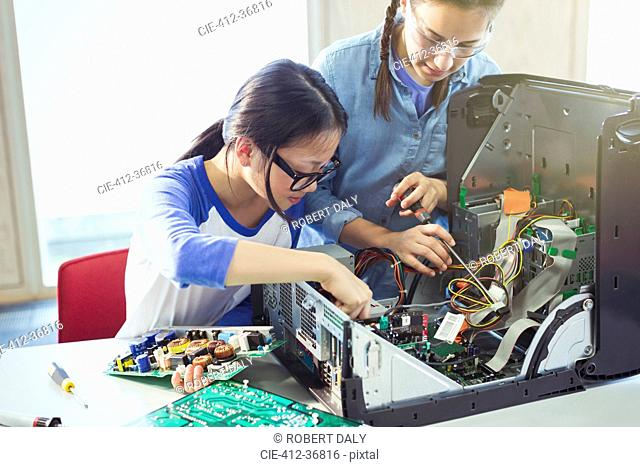 Girl students assembling computer in classroom