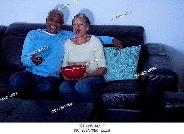 Senior couple sitting on sofa at night, watching television, woman holding bowl of popcorn