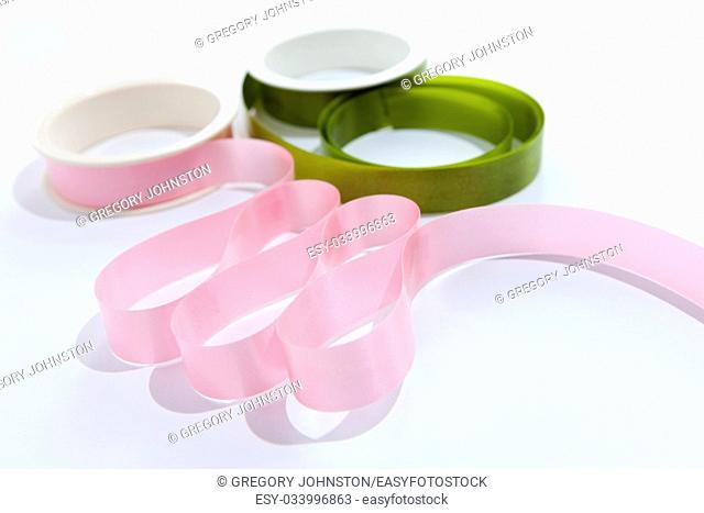 Pink and green ribbons unfurled from their spools