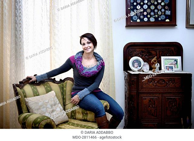 The open water swimmer Monica Priore posing sitting on the arm of an armchair in her living room. She's afflicted with type 1 diabetes since 33 years and she...