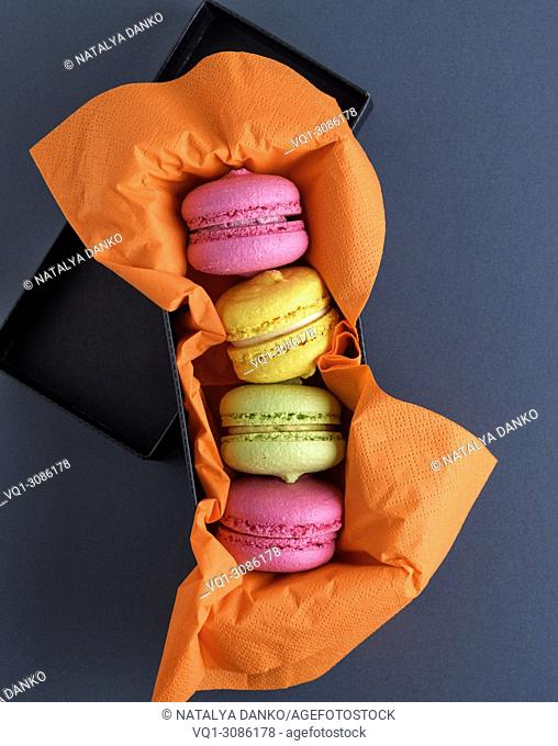 multicolored macarons on an orange napkin, top view