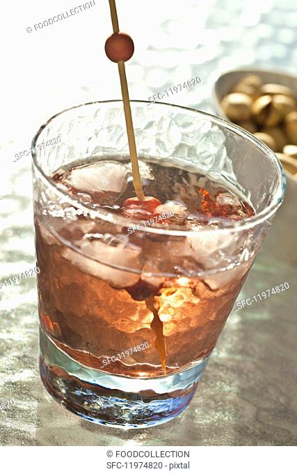 A whiskey cocktail with cherries