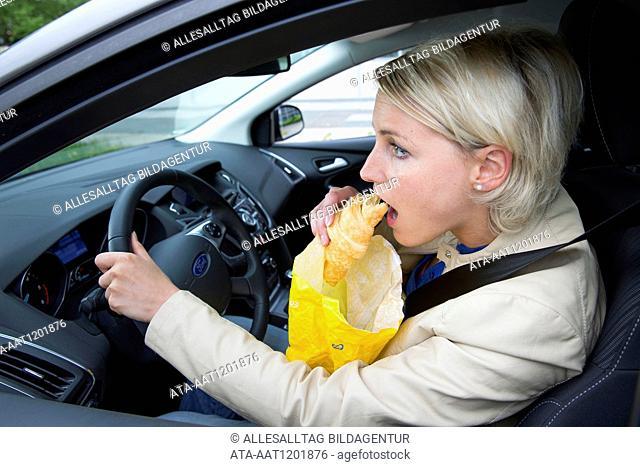 Female car driver eats a croissant