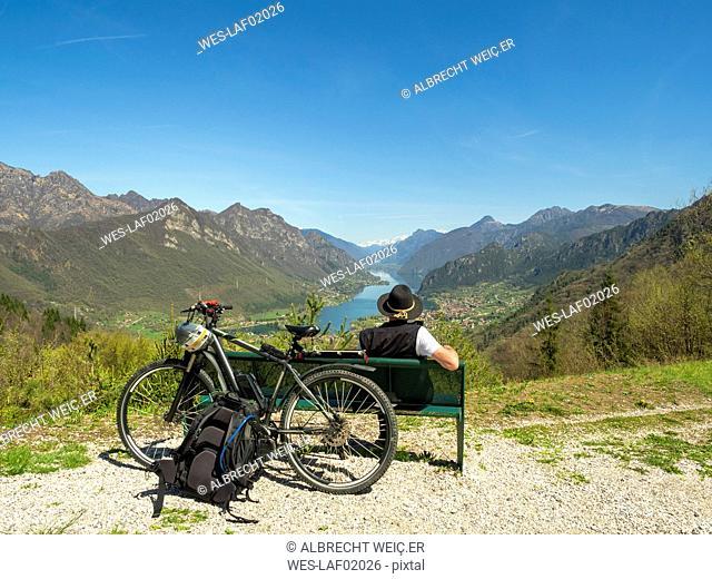 Italy, Lombardy, Senior hiker looking over Idro lake, Adamello Alps, Parco Naturale Adamello Brenta