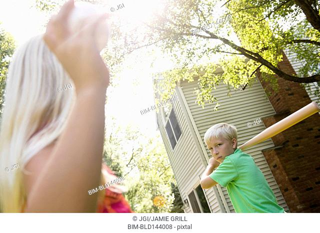 Caucasian children playing baseball in backyard