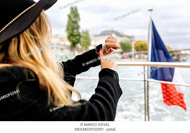 Paris, France, tourist taking a cruise on Seine River using smartwatch