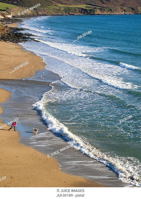 Woman and dog enjoying beach and ocean at Gerrans Bay, Cornwall, United Kingdom