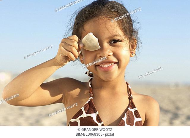 Young mixed race girl holding shell at beach