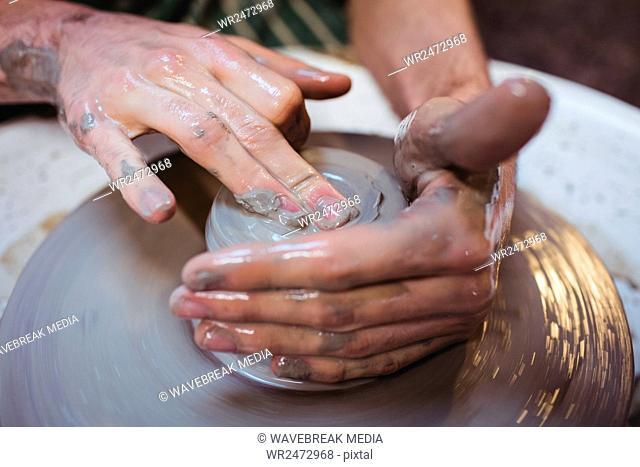 Cropped image of craftsperson in potter workshop