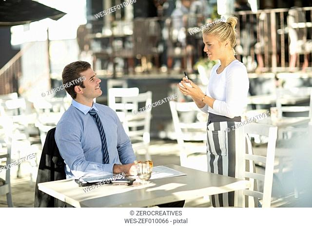 Businessman and waitress at outside restaurant
