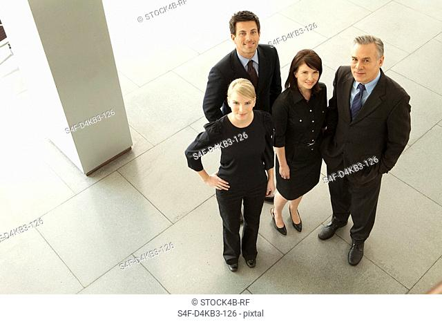 Four confident businesspeople in lobby, Munich, Bavaria, Germany