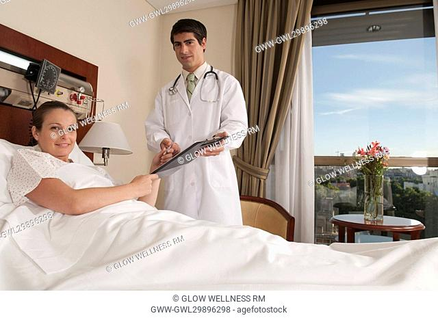 Woman taking clipboard from a doctor in a hospital