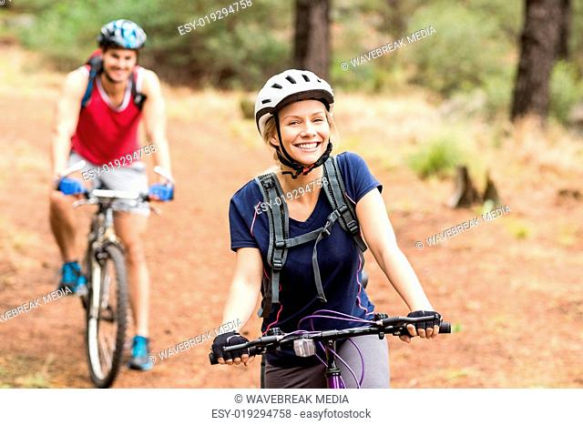 Happy young biker couple looking at camera