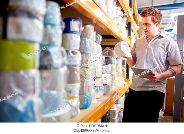 Factory worker stock taking using digital tablet in roller blind factory