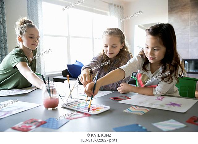 Girls enjoying play date painting at dining room table