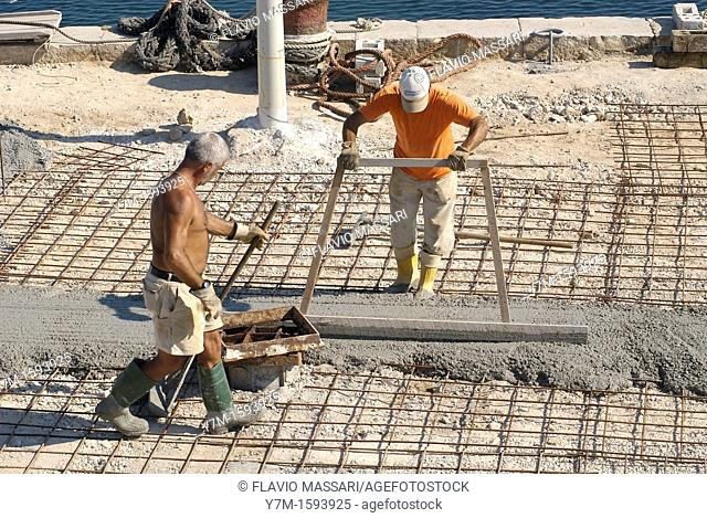 Gallipoli Italy: workers pouring concrete at the port docks