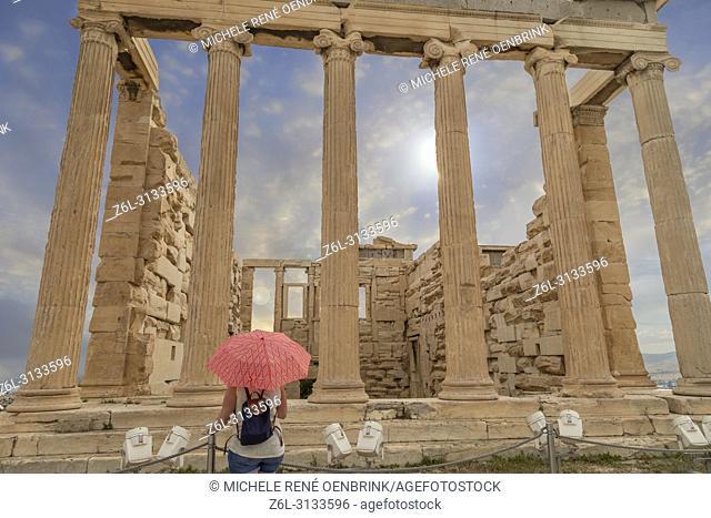 Tourist woman with umbrella at The Parthenon or Temple of Athena on Athenian Acropolis in Greece