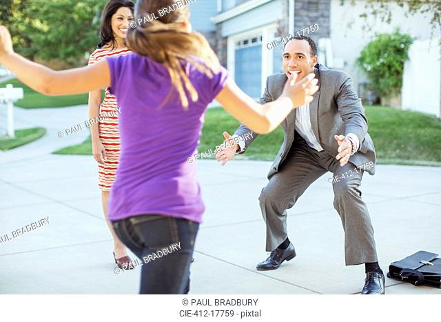 Daughter running to father in driveway