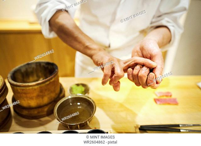 A chef working in a small commercial kitchen, an itamae or master chef pressing rice into shape for making sushi