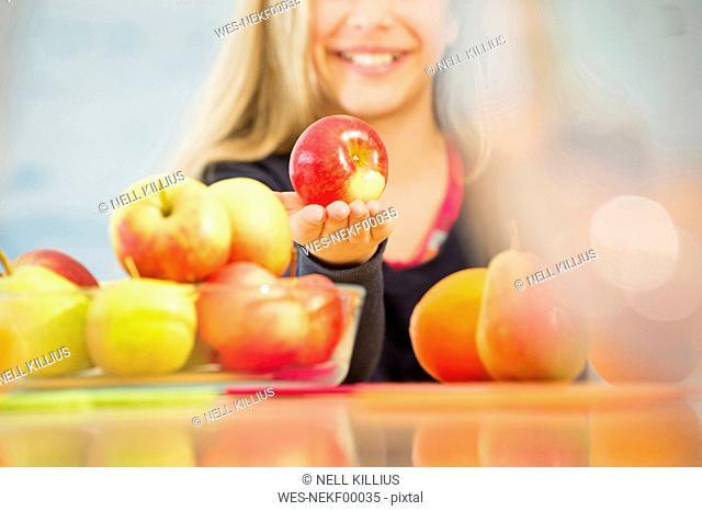 Smiling girl offering an apple