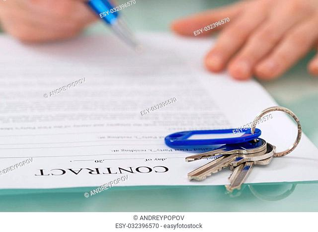 Close-up Of Contract With Key On Desk