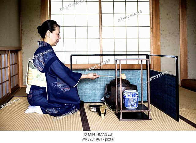 Japanese woman wearing traditional bright blue kimono with cream coloured obi kneeling on floor, using a Hishaku, a bamboo ladle, during a tea ceremony