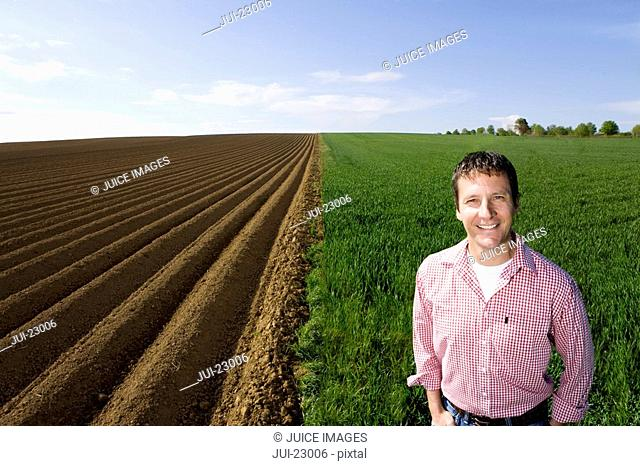 Smiling farmer standing in young wheat field next to ploughed field