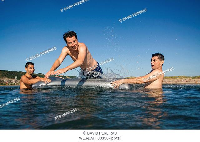 Three playful friends with airbed in the sea
