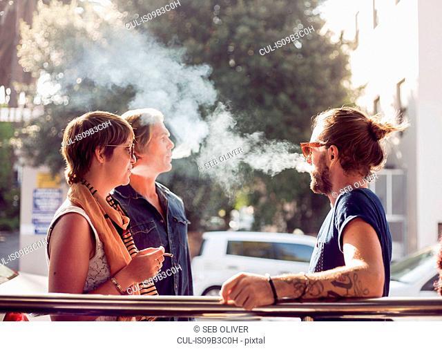 Three friends taking a cigarette break on sidewalk, Cape Town, South Africa
