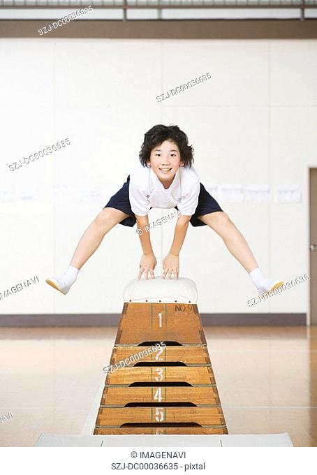 Elementary student jumping over vaulting box