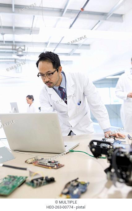 Serious engineer working at laptop near robotics