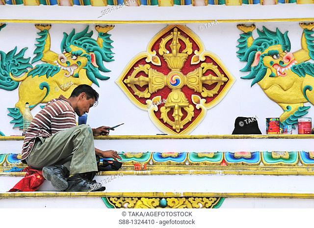 Man restore painting at Tsuglagkhang Temple