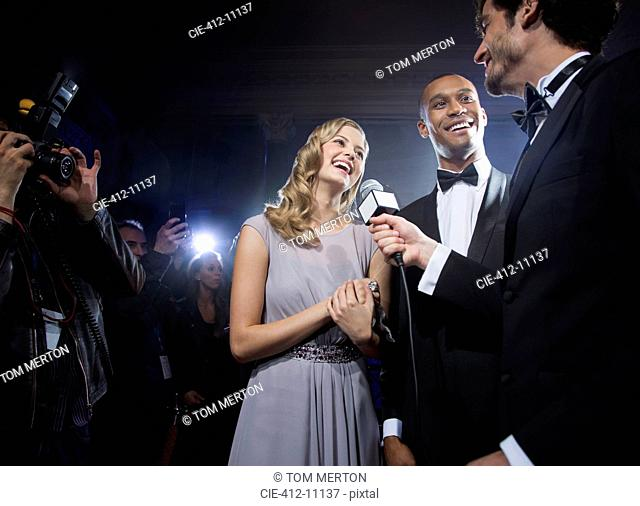 Well dressed celebrity couple being interviewed at red carpet event
